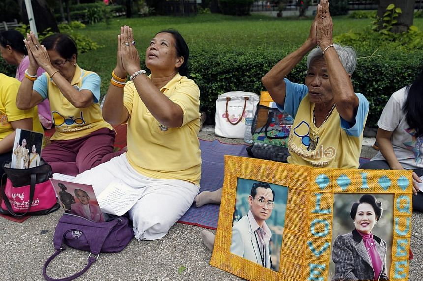 Well-wishers gather outside Siriraj Hospital in Bangkok yesterday with portraits of King Bhumibol Adulyadej and his wife Queen Sirikit to pray for the monarch's health.