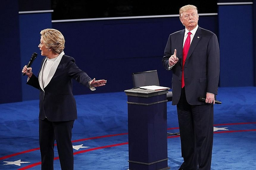 Mrs Clinton and Mr Trump during their second presidential debate, held at Washington University in St Louis, Missouri, on Sunday. Pundits felt that Mr Trump did better than expected, while his rival played it safe throughout the 90-minute debate. Sti
