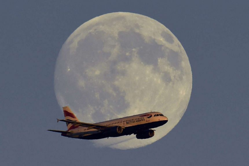 A British Airways passenger aircraft passes in front of the moon as it makes it's landing approach towards Heathrow Airport.