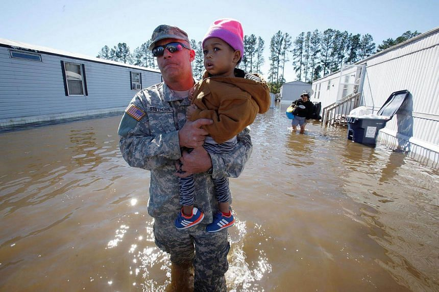 National Guard Sergeant Jeremy Stellhorn carries two-year-old Cathalawa Olivia through floodwaters after Hurricane Matthew hit the state of North Carolina.