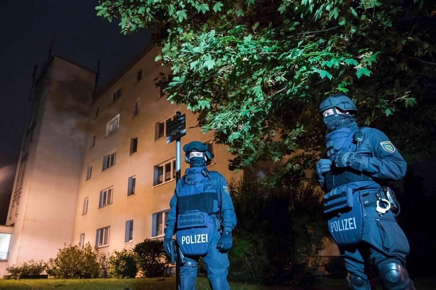 "Policemen in protective clothing stand in front of a residential building in Chemnitz, eastern Germany. Police found several hundred grams of ""explosive materials"" in the east German apartment of a Syrian man suspected of planning a bomb attack and h"