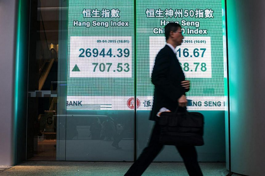 A pedestrian walks past an electronic display showing the closing figure of the Hang Seng Index outside the Hang Seng Bank Ltd. headquarters in Hong Kong.