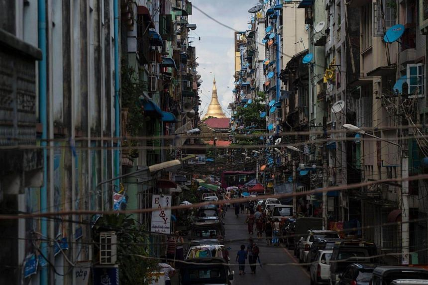 The gold dome of Shwedagon pagoda, Myanma's Buddhist religious landmark is seen through a stretch of a road in Yangon.