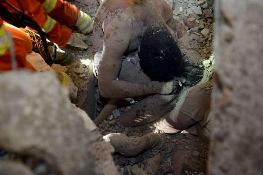 Rescuers trying to save a young girl who was shielded from falling rubble by her father on Oct 10, 2016.