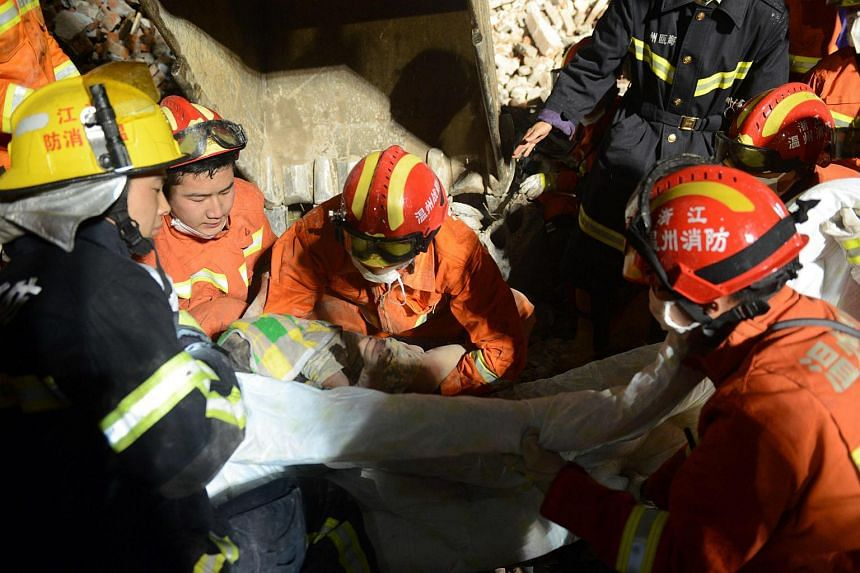 Rescuers carrying a young girl who was rescued at an accident site after four buildings caved in during the early hours in Wenzhou, China on Oct 10, 2016.