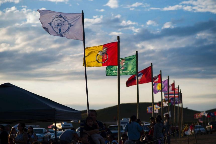 Flags of Native American tribes from across the US and Canada line the entrance to a protest encampment near Cannon Ball, North Dakota on Sept 3, 2016.