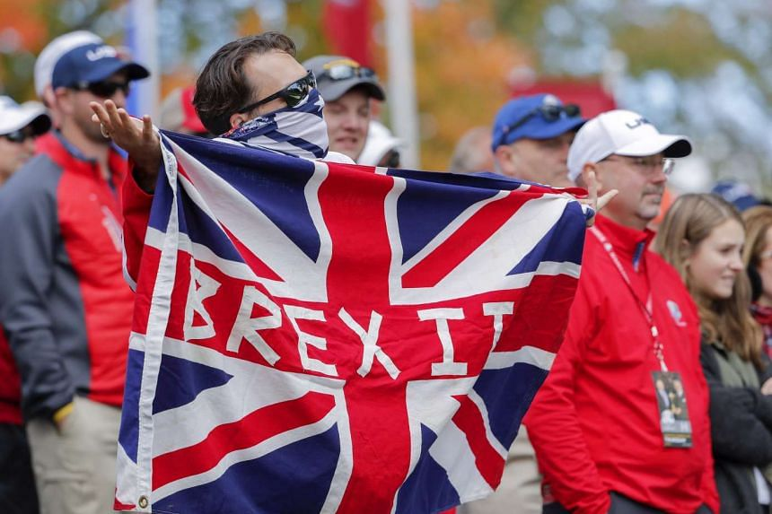 A golf fan holds a Brexit flag during practice for the 2016 Ryder Cup at Hazeltine National Golf Club in Chaska, Minnesota, USA, on Sept 29, 2016.