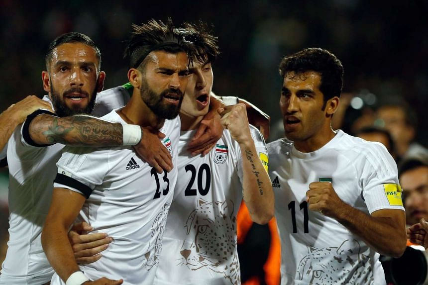 Iran's Sardar Azmoun (second from right) celebrates with teammates after scoring.