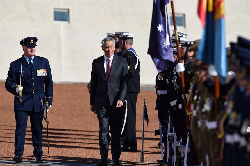 Prime Minister Lee Hsien Loong inspects a guard of honour during the ceremonial welcome at Canberra's Parliament House.