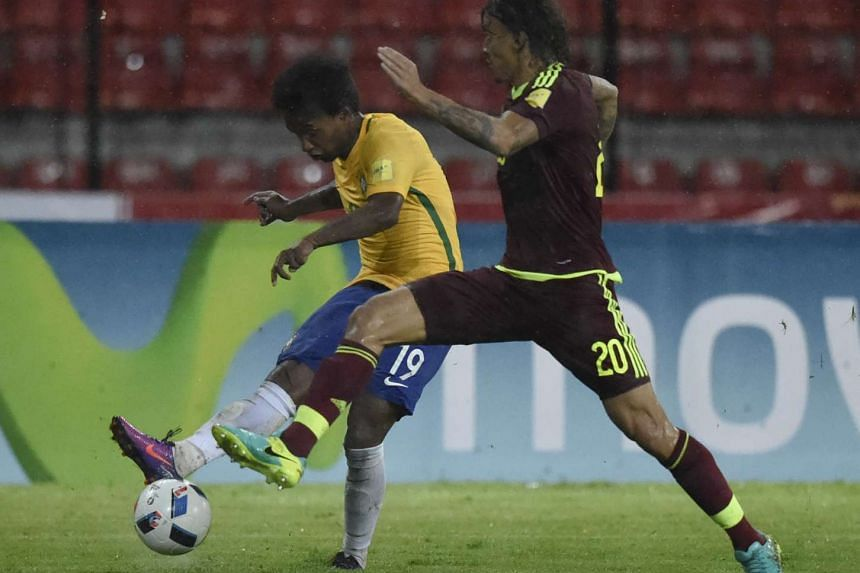 Brazil's Willian (left) vies for the ball with Venezuela's defender Rolf Feltscher during their Russia 2018 World Cup football qualifier match in Merida, Venezuela, on Oct 11, 2016.