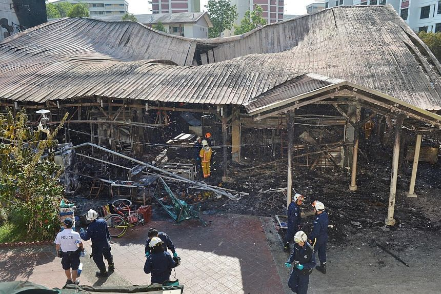 The charred remains of the coffee shop and wet market at Block 493, Jurong West Street 41, after the blaze was put out yesterday morning. A coffee shop at Block 494 was also damaged. Residents from the surrounding blocks were evacuated at the height