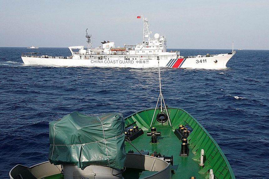 A China Coast Guard ship (top) is seen near a Vietnam marine guard ship in the South China Sea in 2014. A new security framework can help avoid tense scenes like this, China believes.