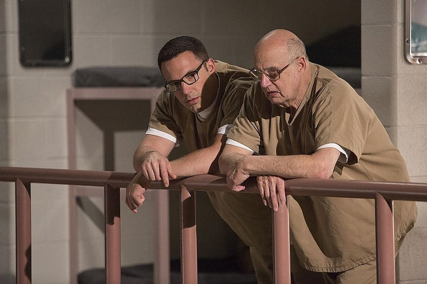 Ben Affleck (left, with actor Jeffrey Tambor) plays a mathematics genius who cooks the books for clients in The Accountant.