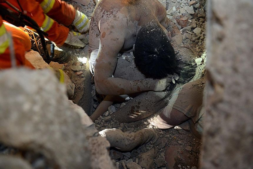 This picture of a man using his body to shield his three-year-old daughter from harm is one of the most touching images to emerge from the building collapse in Wenzhou, in eastern China's Zhejiang province, on Monday. Rescuers found the pair more tha