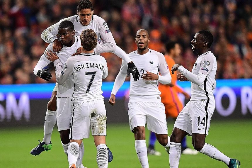 France midfielder Paul Pogba (left) is congratulated by team-mates after scoring from 25 metres out against the Netherlands.
