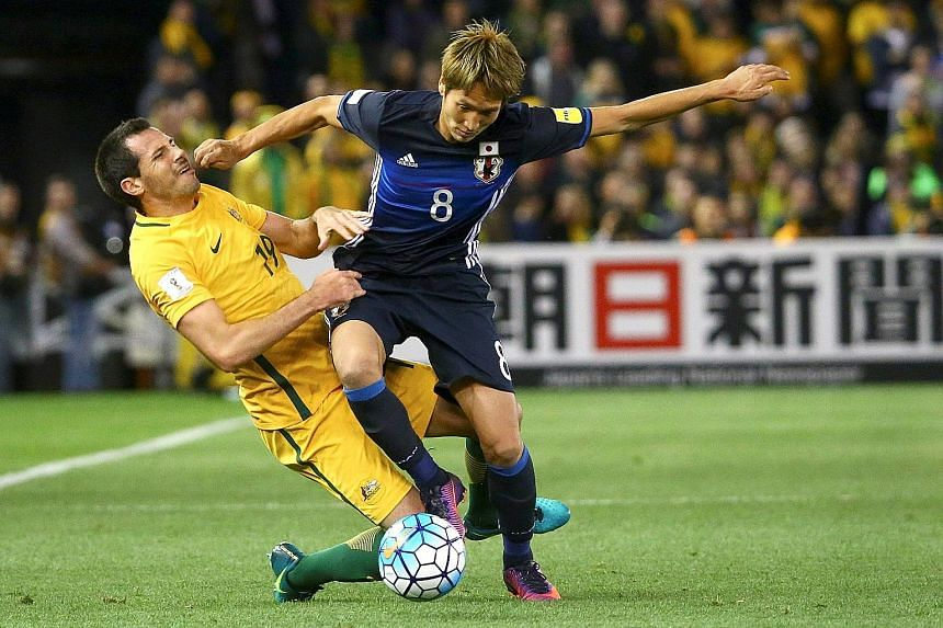 Genki Haraguchi of Japan keeps his balance despite this challenge by Ryan McGowan during the 1-1 World Cup qualifying draw in Melbourne yesterday. Haraguchi was both hero and villain for Japan, as he scored his side's fifth-minute goal before concedi