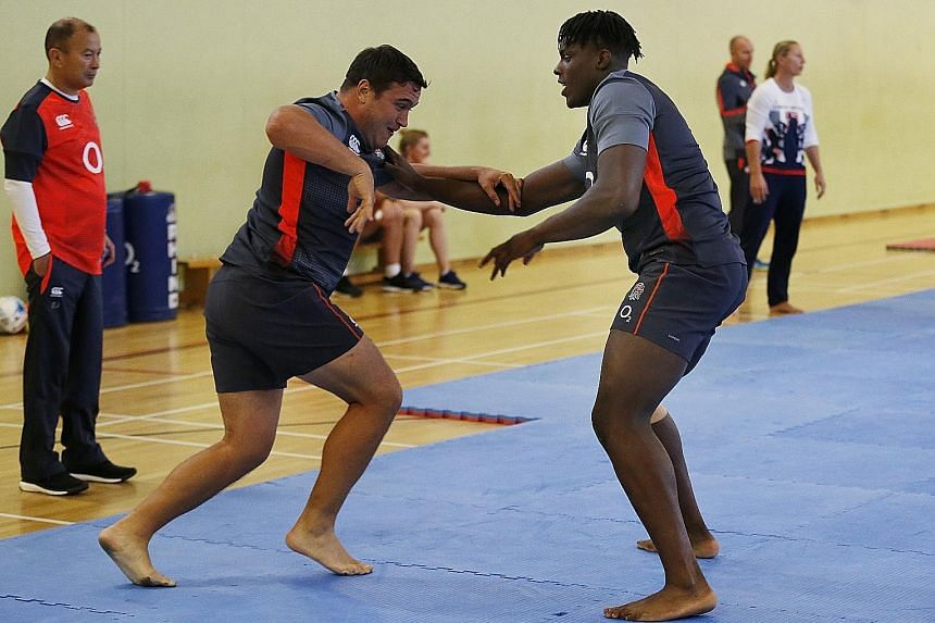 England's Jamie George and Maro Itoje take part in a judo session as head coach Eddie Jones watches on.