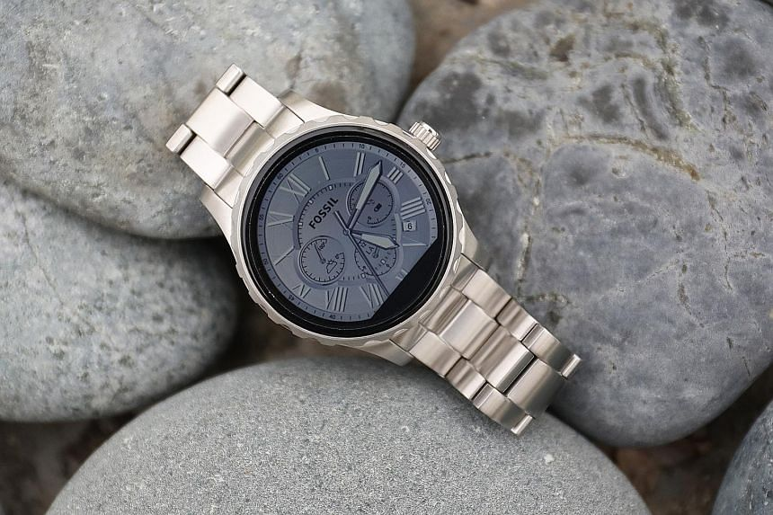 The Fossil Q Marshal can be easily mistaken as a regular analogue watch (left), until you raise your wrist and its touchscreen display comes to life (far left).