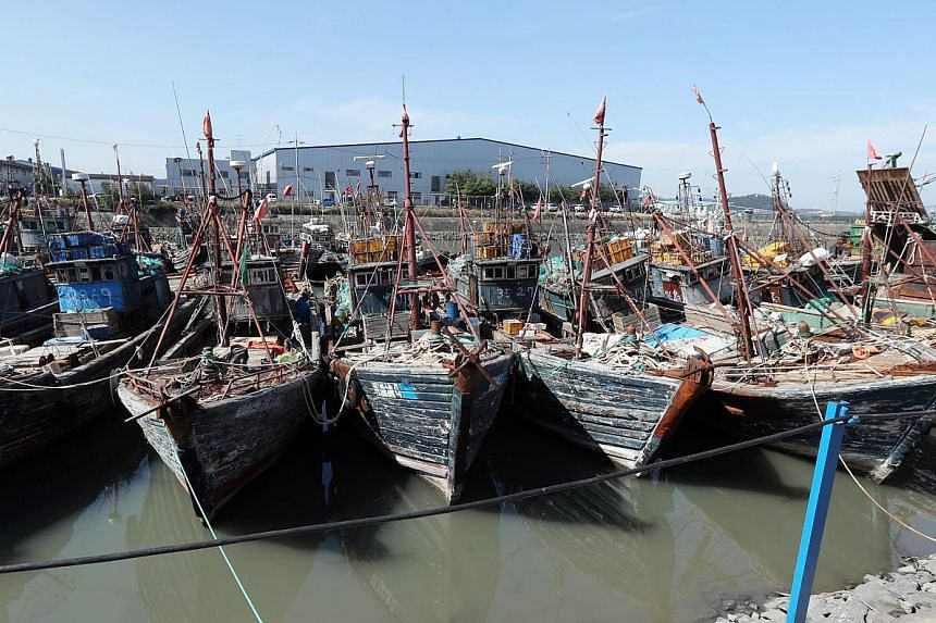 Chinese fishing boats that were seized after being caught operating illegally in South Korea's exclusive waters moored at a port in Incheon, South Korea. The South Korean coast guard plans to relax its rules on the use of firearms.