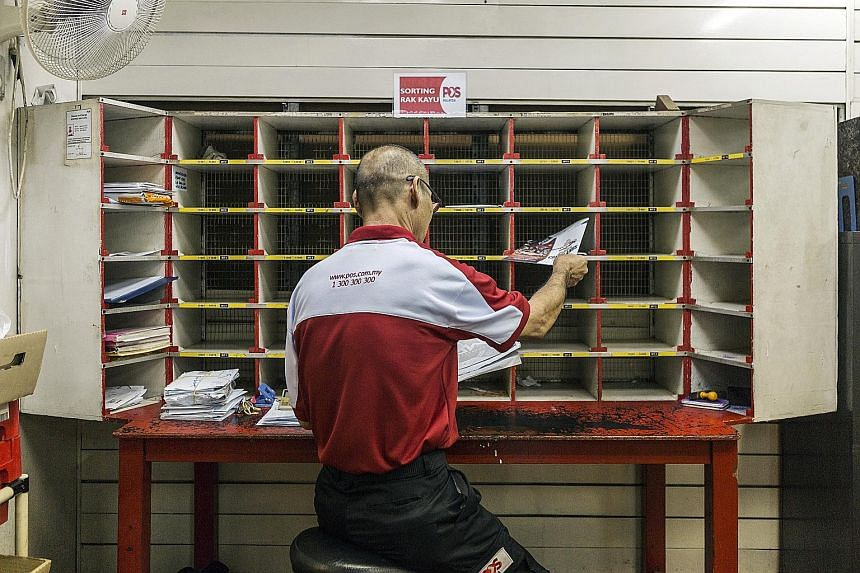 A Pos Malaysia employee sorting mail in a post office in Kuala Lumpur. Increased parcel deliveries due to online shopping drove a 40 per cent jump in the company's profit in the fiscal first quarter.