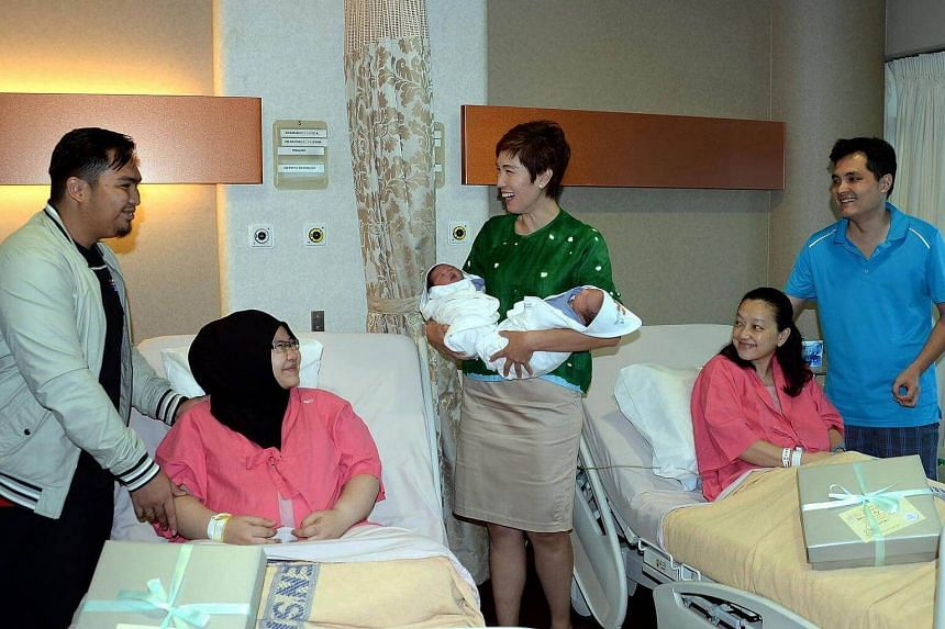 Ms Josephine Teo (centre), Senior Minister of State at the Prime Minister's Office, carrying the first 2016 baby, Khairy Rusyaidy (left) and the last SG50 baby, Ansley Soong (right) at Kandang Kerbau Hospital (KKH) on Jan 1, 2016.