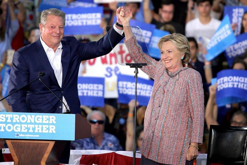 Former Vice President Al Gore (left) shakes hands with US Democratic party's presidential candidate and former Secretary of State Hillary Clinton (right) during her Presidential campaign at Miami Dade College in Miami, Florida, USA on Oct 11, 2016.