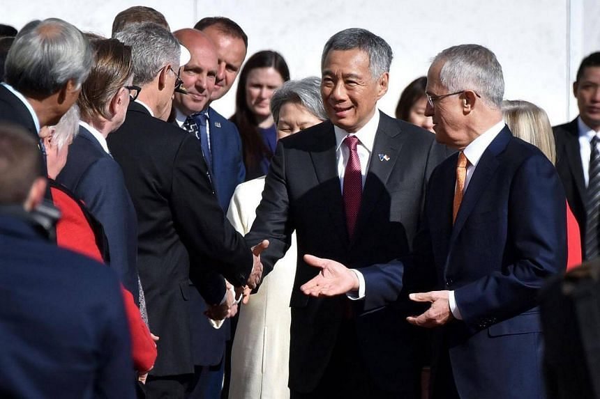 PM Lee Hsien Loong is introduced to members of the Australian Government by Australian PM Malcom Turnbull during the ceremonial welcome outside Canberra's Parliament House.