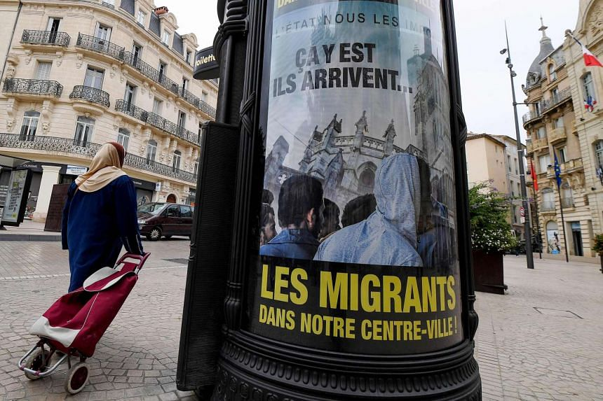 A woman walks past anti-migrant posters in the centre of Beziers on Oct 12, 2016.