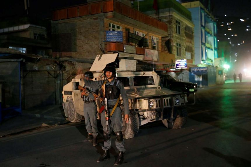 Afghan policemen stand guard near the site of an attack in Kabul, Afghanistan Oct 11, 2016.