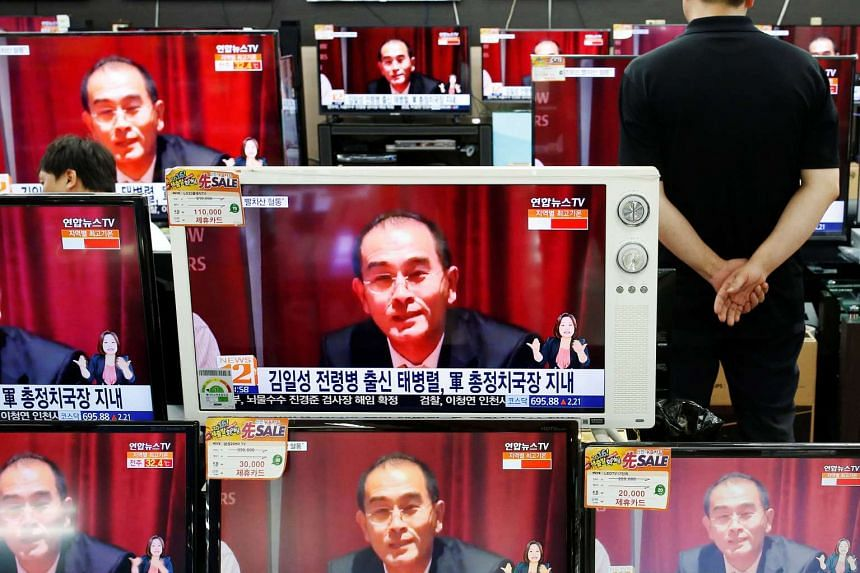 A sales assistant watches TV sets broadcasting a news report on Thae Yong Ho, North Korea's deputy ambassador in London, who has defected with his family to South Korea.
