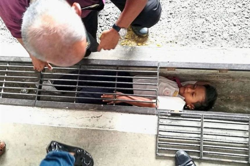 A man trying to calm the eight-year-old boy who got stuck in a drain at his school in Klang.