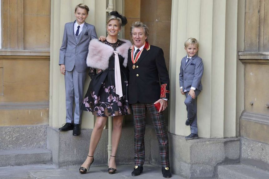 Singer Rod Stewart poses at Buckingham Palace with wife Penny Lancaster and children Alastair and Aiden after receiving his knighthood.