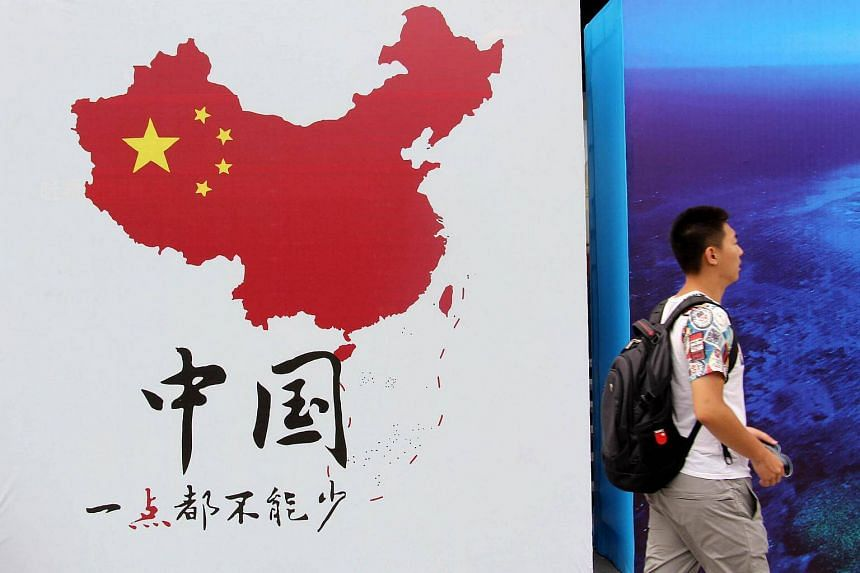 A man walking past a poster of a map. All maps published in China have to show Taiwan as one of the country's provinces.