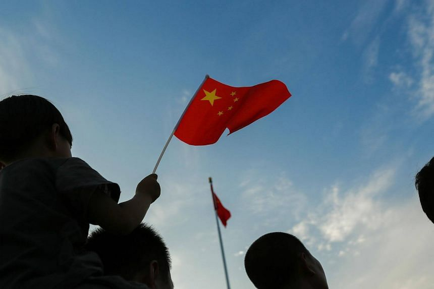 A child waving a Chinese flag during the daily flag lowering ceremony at sunset in Beijing's Tiananmen Square.
