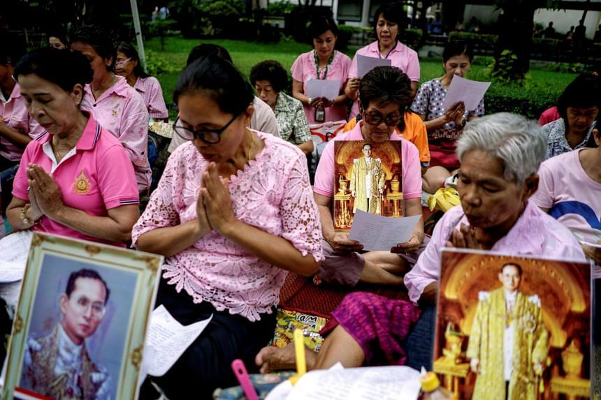 Well-wishers hold pictures of Thailand's King Bhumibol Adulyadej as they pray for him at the Siriraj hospital.