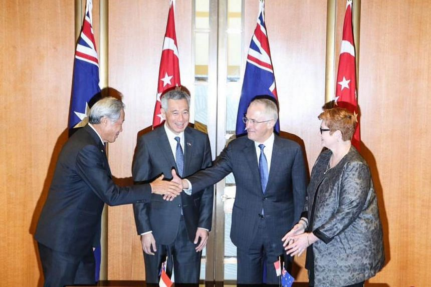 Defence Minister Ng Eng Hen (left) shakes hands with Australian Prime Minister Malcolm Turnbull (second from right) as Prime Minister Lee Hsien Loong (second from left) looks on.