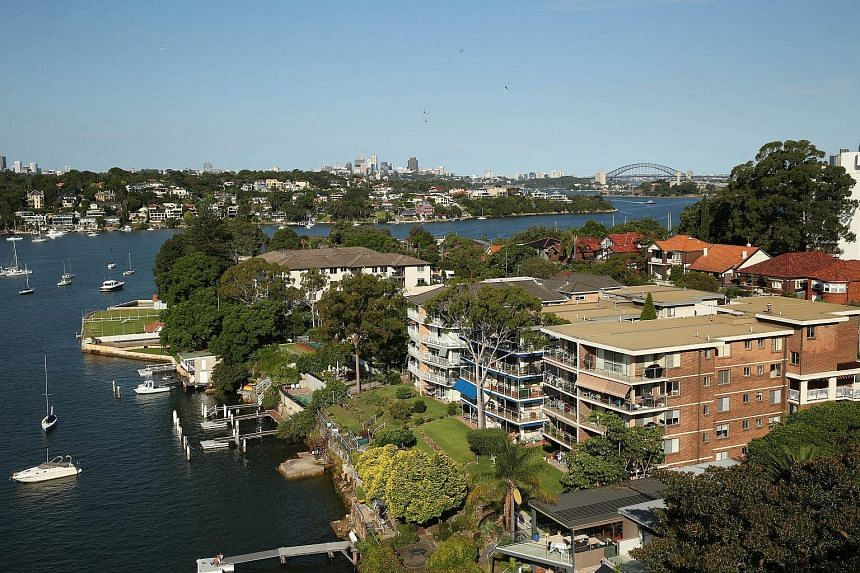 Houses stand by the waterfront as the Sydney Harbour Bridge stands in the distance in Sydney, Australia.