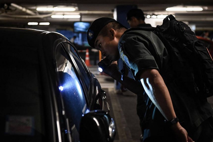 A policeman from the Crime Supression Division unit searches a car in the parking lot of a shopping mall in Bangkok on Oct 11, 2016.