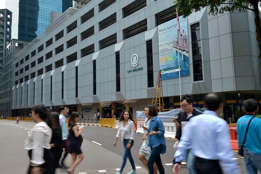 Office workers crossing the road in front of the CPF building in Robinson Road. A national system to certify the skill levels of human resource (HR) professionals will be piloted at the end of this month.