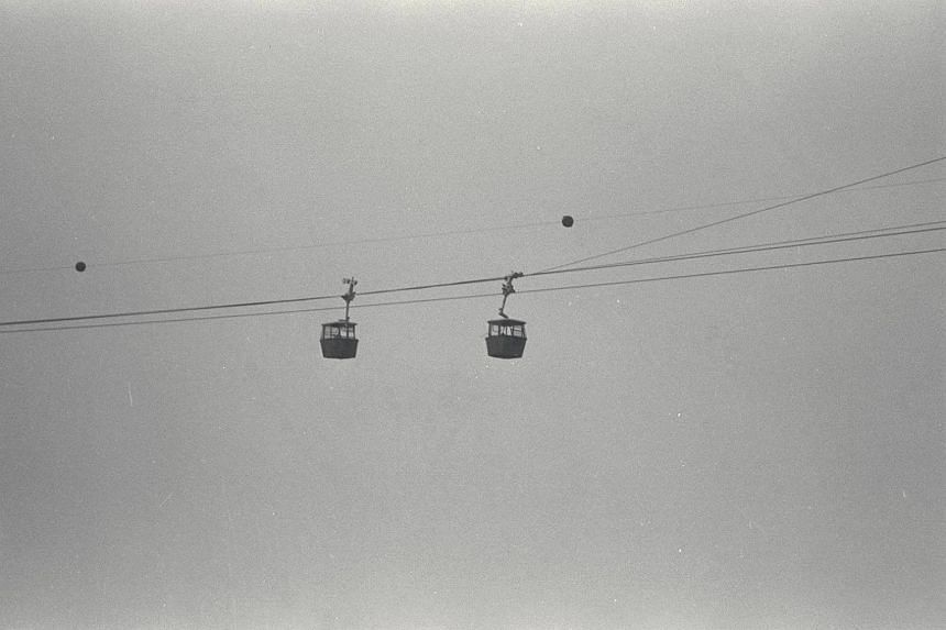 Two of the five cable cars stranded in mid-air, swinging ominously