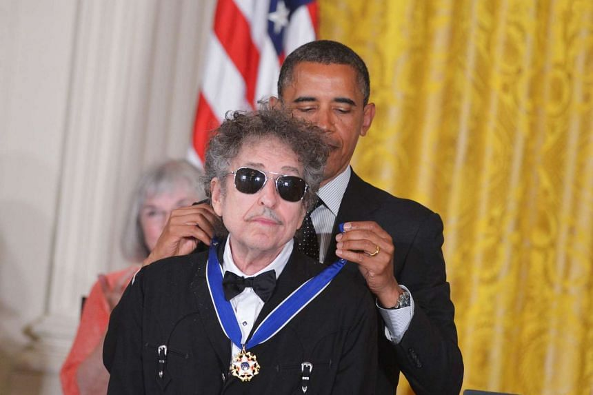 US President Barack Obama (right) presenting the Presidential Medal of Freedom to US musician Bob Dylan in the East Room of the White House in Washington on May 29, 2012.