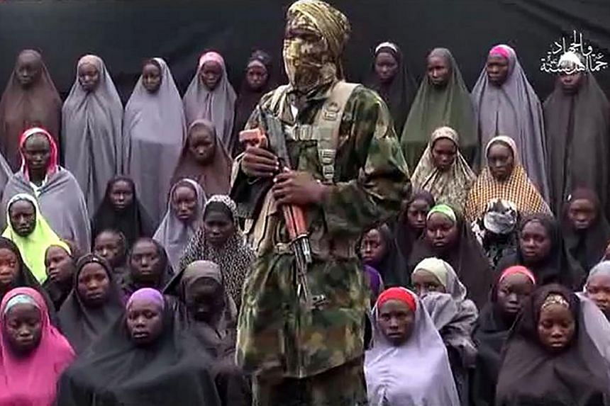 This video grab image created on Aug 14, 2016 from a video on YouTube purportedly by Boko Haram showing what is claimed to be one of the groups fighters standing in front of girls allegedly kidnapped from Chibok in April 2014.