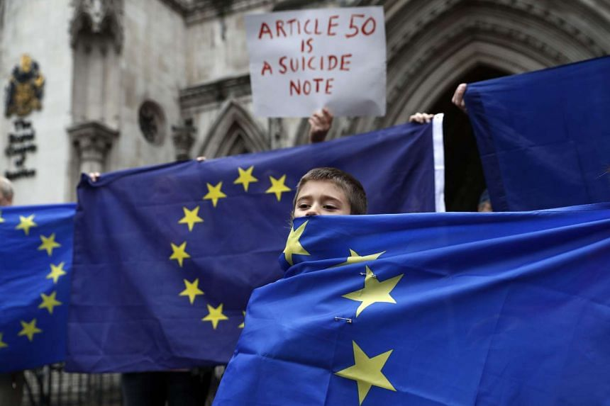 Pro-European Union (EU) supporters stand at the entrance to Britain's High Court in London on Oct 13, 2016, during a protest against the UK's decision to leave the EU.
