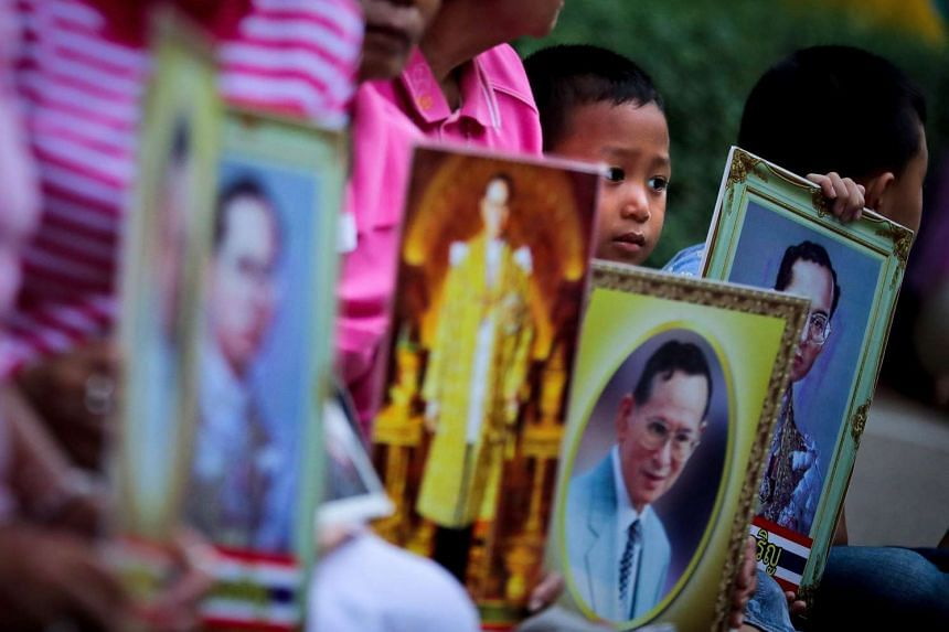 Thai well-wishers pray with portraits of Thai King Bhumibol Adulyadej, wishing for the King's recovery, outside the Siriraj Hospital in Bangkok.