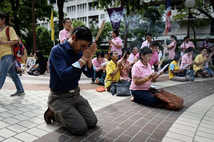 Supporters of Thailand's King Bhumibol Adulyadej pray at the compounds of Siriraj Hospital, where the king is being treated, in Bangkok on Oct 13, 2016.
