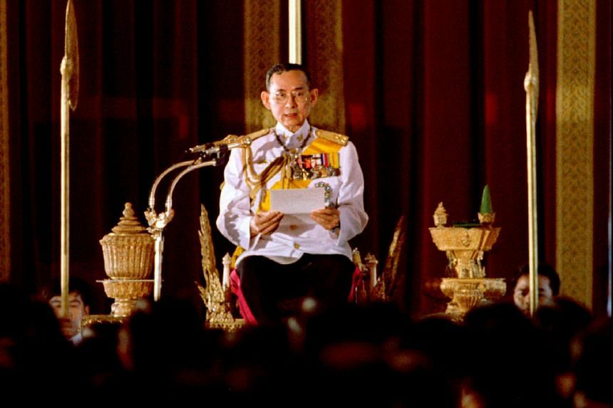 Thai King Bhumibol Adulyadej reads a statement convening Parliament in front of 391 newly elected members of parliament at Ananta Samakhom throne in Bangkok in this July 10, 1995 file photo.