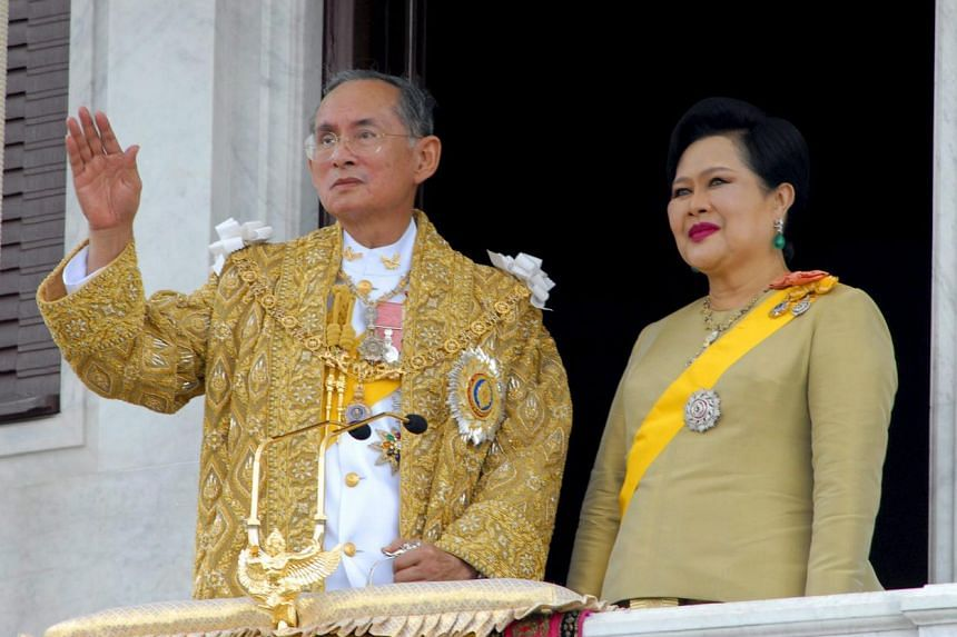 Thai King Bhumibol Adulyadej waving to Thais gathered outside, as Queen Sirikit looks on from the balcony of the Ananta Samakorn Throne Hall in Bangkok on June 9, 2006.