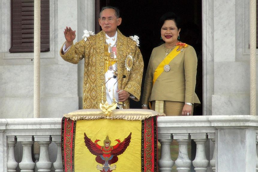 This file photo taken on June 9, 2006 shows Thai King Bhumibol Adulyadej and Queen Sirikit waving to Thais after his address in Bangkok.