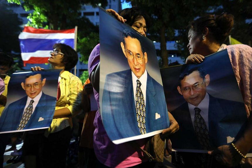 People react as they hold photographs of Thai King Bhumibol Adulyadej outside Siriraj Hospital following the announcement of his death in Bangkok, Thailand, on Oct 13, 2016