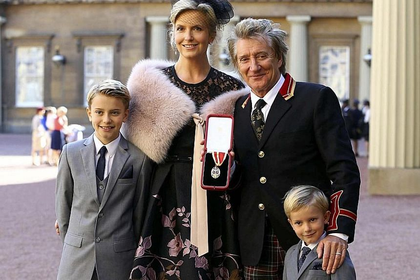 British singer Rod Stewart, 71, at Buckingham Palace with his third wife Penny Lancaster, 44, and two children, Alastair, 10, and Aiden, five, after receiving his knighthood. Prince William knighted him on Tuesday for his services to music and charit